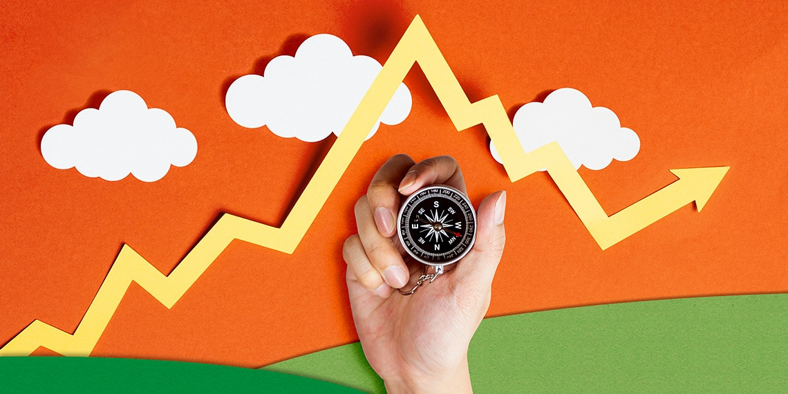 Image of a hand holding a compass beneath a market line chart.